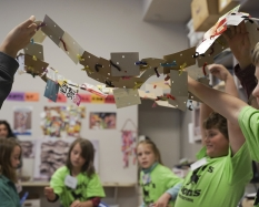 Children wearing green t-shirts stand to the left and right of the photo, holding up artwork they made. The artwork is a string of squares of recycled cardboard and cardstock, with holes punched through. The squares are connected by pipe cleaners.