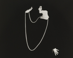 A black and white photograph of a woman in profile (actress Louise Brooks) wearing a long black-sleeved dress, against a black background, holding a long strand of pearls up with her right hand, the necklace is also draped around her neck.