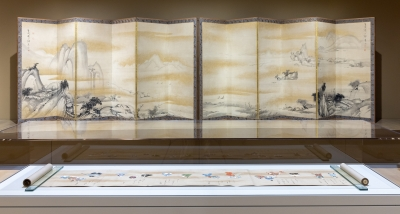 An installation of traditional Japanese art. A 32 foot hand scroll is displayed in the foreground and a large Japanese screen is in the background.
