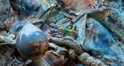 A detail of a sculptural 3D painting that employs cloth, paint, and various found objects.