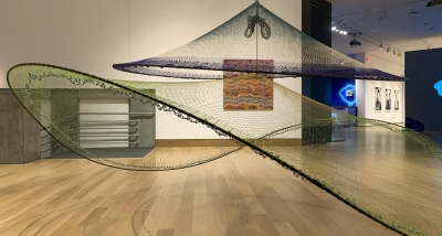 A photograph of an exhibition installation which includes a an Australian Aboriginal painting and a large netted sculpture that hangs from the ceiling.