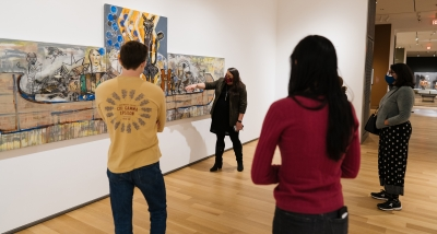 A photograph of four adults in a museum gallery. Two have their backs to the camera, one is in profile, and the fourth is speaking to the others about a large painting.