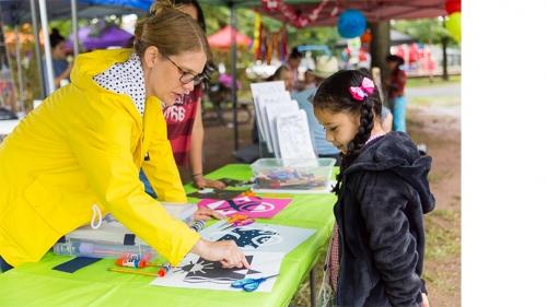 Amanda Potter '02 helps a young artist at a community event