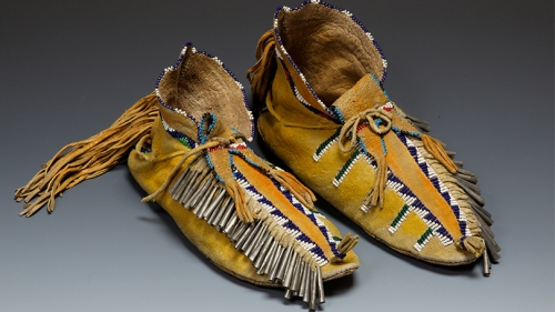 Moccasins made by a Jicarilla Apache artist, about 1900, Native-tanned hide, rawhide, glass beads, tin, ochre, thread.