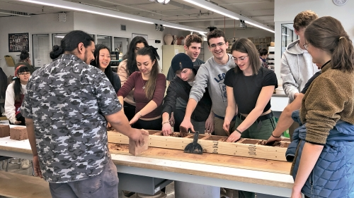 A photograph of a group of college students standing around a long table making clay bricks from a mold.