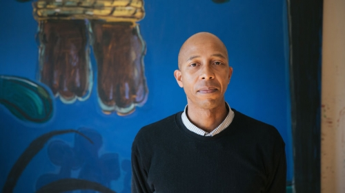 Enrico Riley in front of one of his paintings