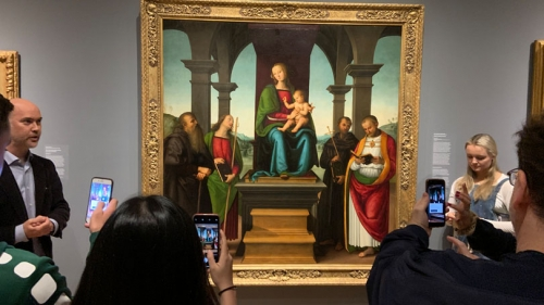 With Associate Professor of Art History Nicola Camerlenghi, left, students test out the new Augmented Dartmouth app on Perugino's Virgin and Child with Saints in the Hood Museum of Art.