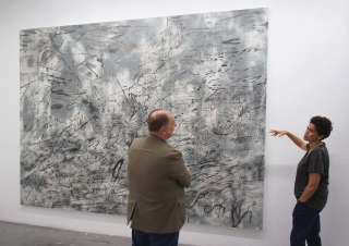"""Director John Stomberg and artist Julie Mehretu discuss """"Iridium over Aleppo"""" in her New York studio in May 2018, while the commission was still in progress. Photo by Alison Palizzolo."""