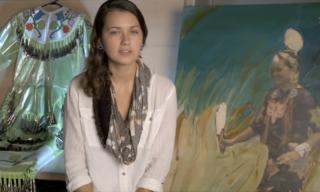 Studnet being interviewed in front of Native American art pieces