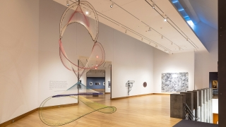 A photograph of a museum gallery and installation of contemporary art, including a large kinetic sculpture made of colorful netting in the foreground.