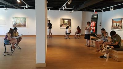 A Dartmouth undergraduate French class working with photographs by Julie Blackmon in the Hood Downtown exhibition The Everyday Fantastic.