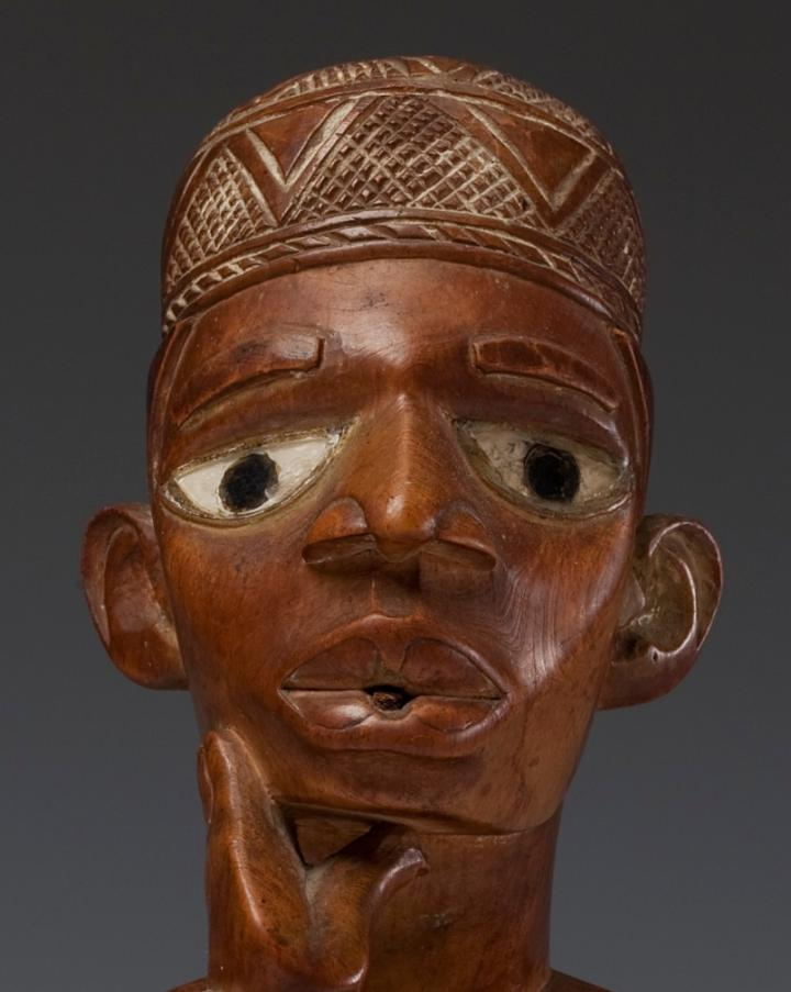 Detail wooden African sculpture of a seated figure made by the Yombe people
