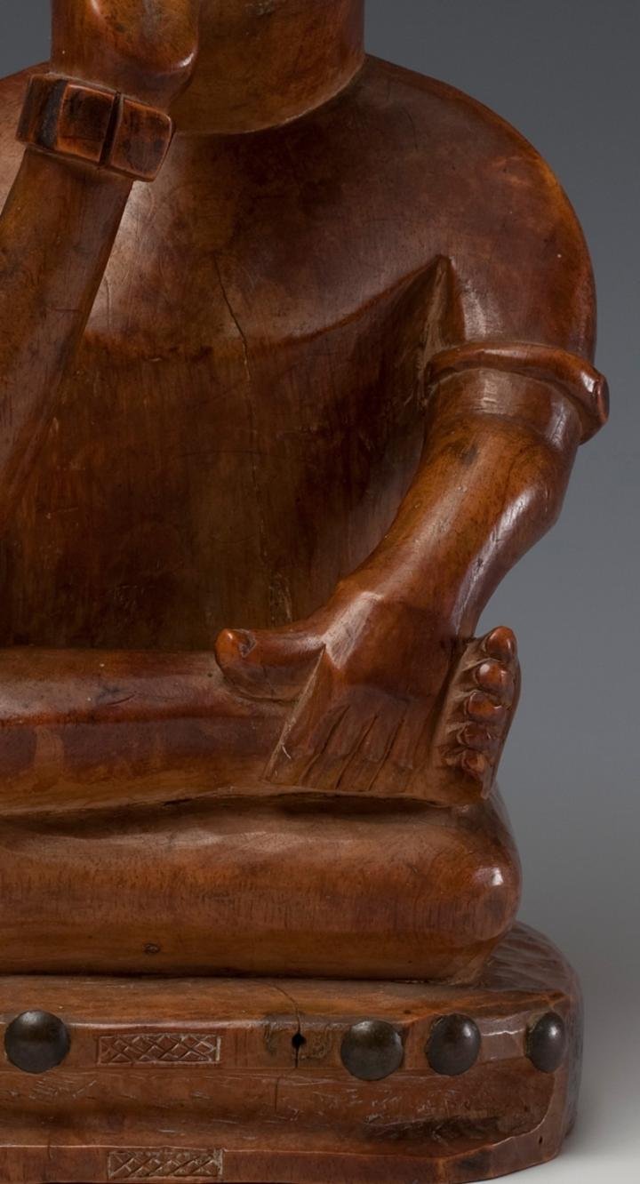Detail front, wooden African sculpture of a seated figure made by the Yombe people