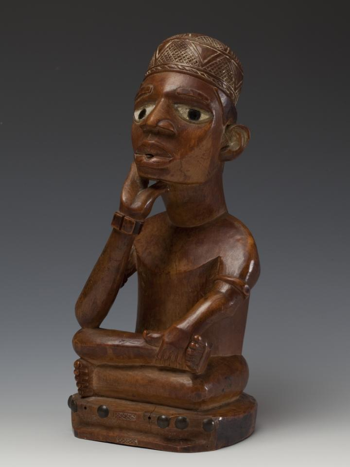 SIde view of a wooden African sculpture of a seated figure made by the Yombe people