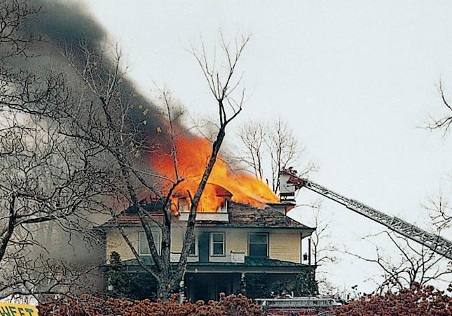 Yellow house with flames and smoke coming from the roof