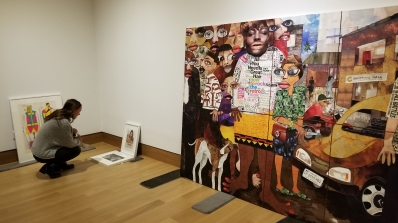 A student crouches in front of several artworks propped up against a wall.