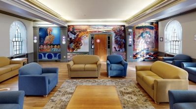 A dormitory common room with blue chairs and tan couches in the center, surrounded by colorful murals.
