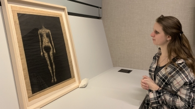 A young woman looking at a framed work of art on paper, that depicts a nude woman, without any features, on a black background.