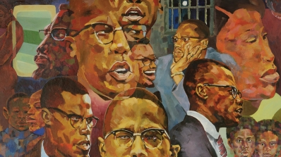 A painted mural depicting portraits of people of color, their ages vary. The portraits are from the shoulders or neck up and are looking in different directions. Malcolm X is shown multiple times.
