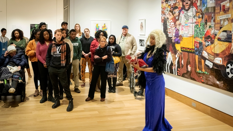 In the galleries, a Black woman wearing a cerulean blue dress, blonde wig, and black jacket stands at the center-right of the photograph, performing to a crowd that is situated to the center and left. Behind the woman is a large mixed-media artwork.