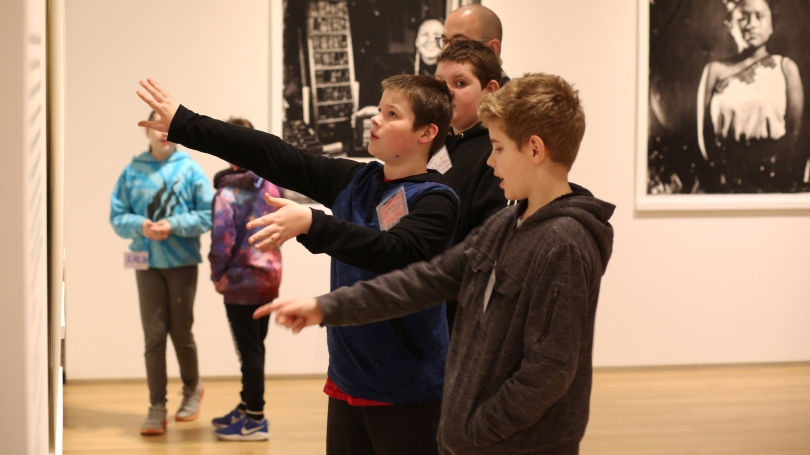 In the galleries, three boys stand at the center of the photo. Two of the boys gesture to an unseen black-and-white photograph that is hung on the gallery walls. In the background, two students browse the exhibition.