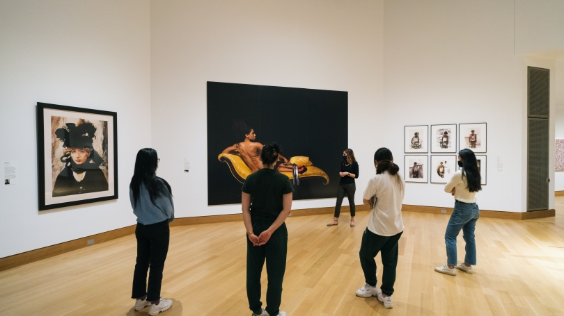 In the galleries, four students stand in a row. They are all listening to Isadora, who is at the center of the photograph, towards the background. Isadora is discussing Renee Cox's Baby Back, a large photograph depicting a reclining nude Black woman.