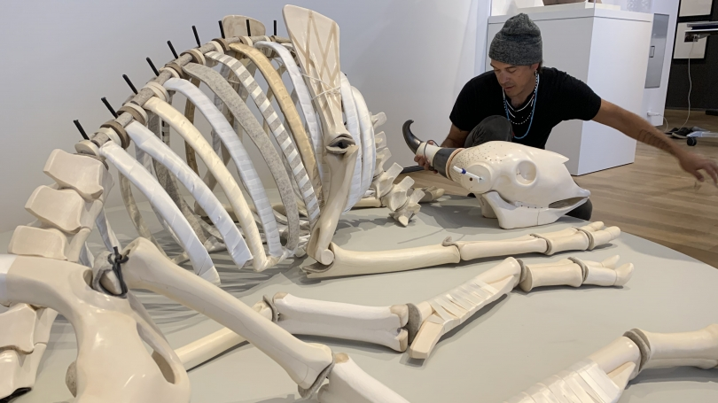 A man is on the right side of the image, leaning over a large white ceramic sculpture of a buffalo skeleton on a pedestal. The sculpture is oriented so that the rear of the buffalo is towards the camera and the head is towards the man.