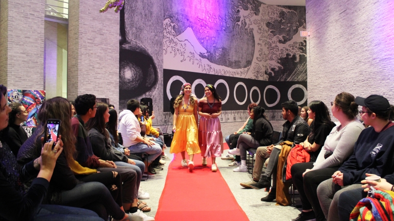 At the center of the photo, two laughing women in a yellow dress (left) and a pink dress (right) stroll down a light red carpet. On either side of the photo, college students sit in rows watching them walk.