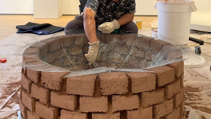 At the center of the photo, a man crouches over a circular clay brick fire pit sculpture. The bricks are a light brown, tinged with red, and there is netting spread over the top. The man, an artist, is putting the final touches on his sculpture.