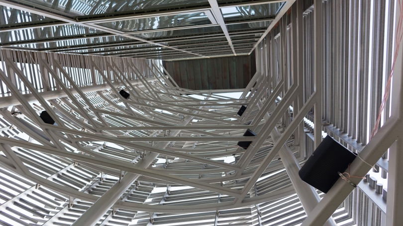 Fig. 13. Interior view, looking up from the ground, of the slatted structure that held six speakers playing sounds recorded from inside the building in Bill Fontana's MicroSoundings, 2017, Class of 1978 Life Sciences Center. Photo by Joseph Beaudoin.