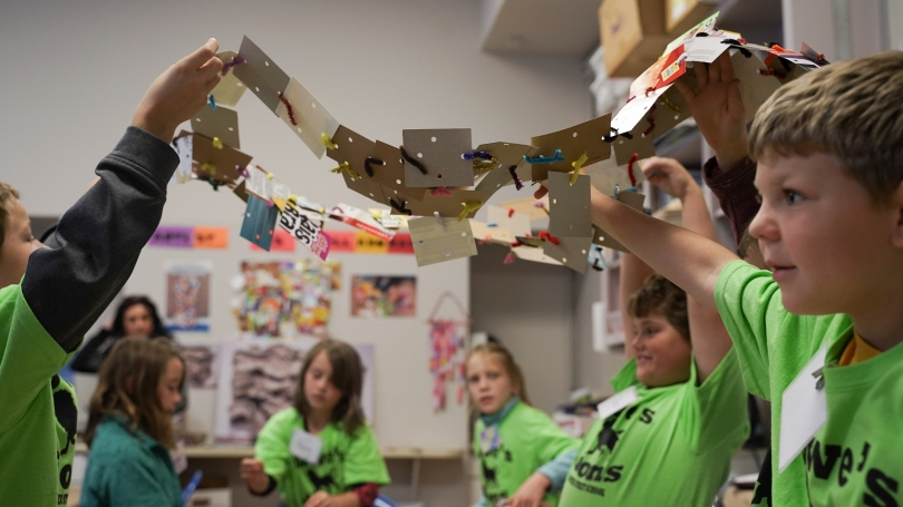 """A third grade class from Hanover Street School works together to create a large scale work of art made from recycled materials inspired by El Anatsui's Hovor as part of their """"Artist as Collaborator lesson."""" Photo by Brian Wagner."""