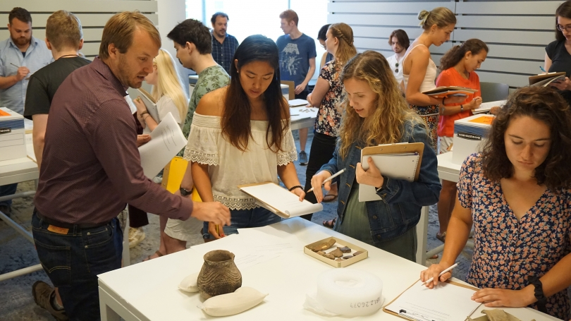 Students in Nathaniel Kitchel's Introduction to Archaeology compare sherds and complete vessels. Photo by Randall Kuhlman.