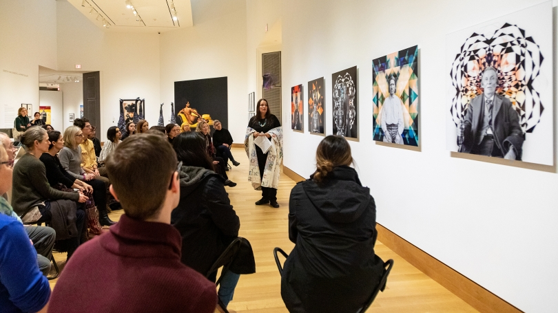 "Artist Gina Adams reads from the 1867 Treaty with the Chippewa, during her ""Broken Treaty Reading Performance"" on February 21, 2020. She is standing in front her of Ancestor Beadwork Prism series. Her performance was followed by a brief Q&A."
