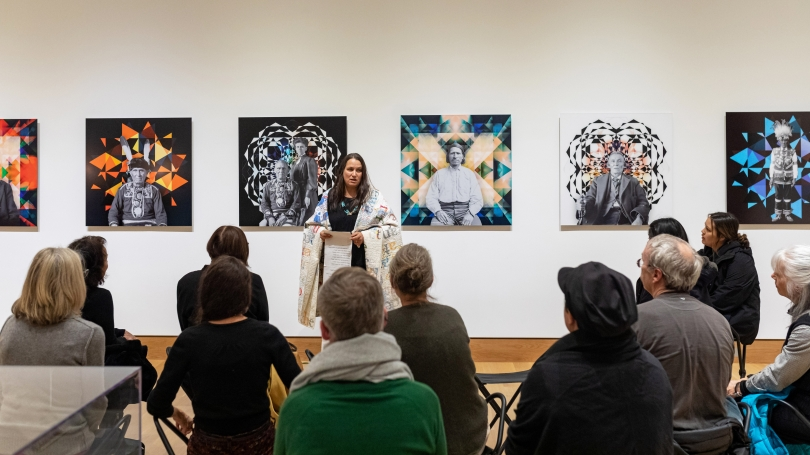 """Artist Gina Adams performs a reading from the Treaty with the Chippewa 1867 Broken Treaty Quilt in front of her """"Ancestor Beadwork Prism"""" works. Photo by Lars Blackmore."""
