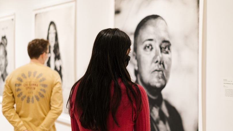 Two viewers look at a large black and white photograph. Their backs are to the camera.