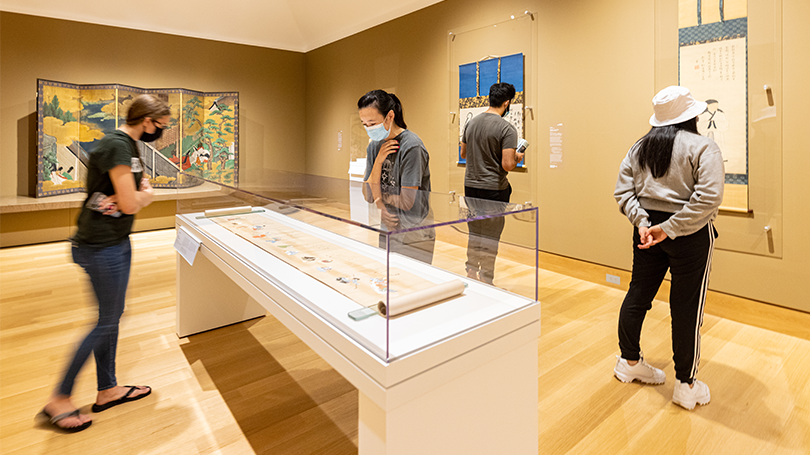 Four students look at traditional Japanese art on view in a gallery with brown walls.