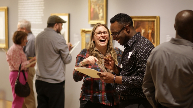 A man and a woman stand at the center of the gallery, laughing together. In the background, other viewers look at artworks on the wall. This is from an art after dark event.
