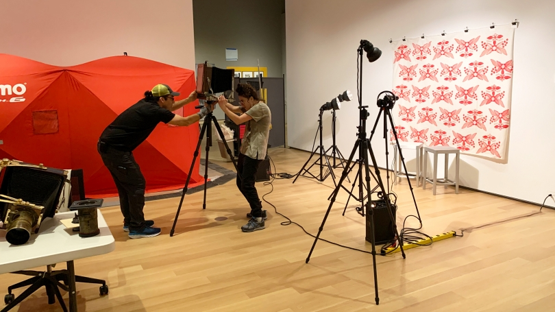 Artists Wil Wilson and Kali Spizter set up a large camera in the gallery. Behind them is a red tent used as a temporary darkroom. To the right are several large lights on tripods.