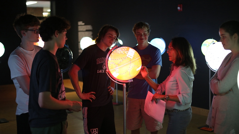 Hood Docent Judy Oxman discusses the Hood Downtown exhibition Ingo Günther: World Processor with students from Hanover High School.