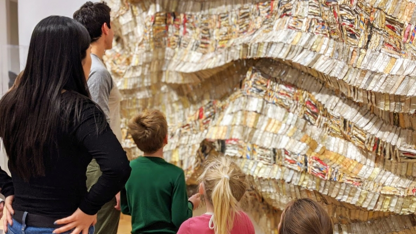 """Dartmouth student mentors and mentees in the Directing through Recreation, Education, Adventure, and Mentoring (DREAM) program visit the museum to discuss El Anatsui's """"Hovor"""" (2003). Photo by Cristina Carpentier."""
