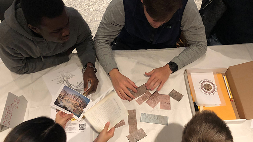 Aerial view of students sitting around a table playing the museum's Assyrian Relief Escape Room Challenge.