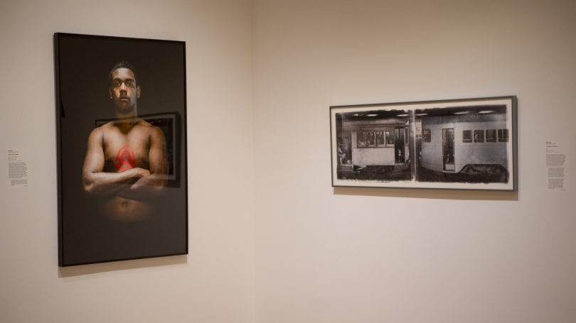Portrait of a young man with a painted target in the center of his chest hanging next to photograph of subway cars.