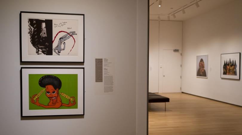"""Two works hanging on the wall. The top work reads """"They will torture you my friend,"""" while the bottom work shows a mangled human like figure with a sombrero."""