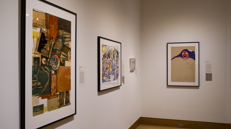 The works hanging on the gallery wall including a collage, a painting of soldier-like individuals, and an opened mouth individual.