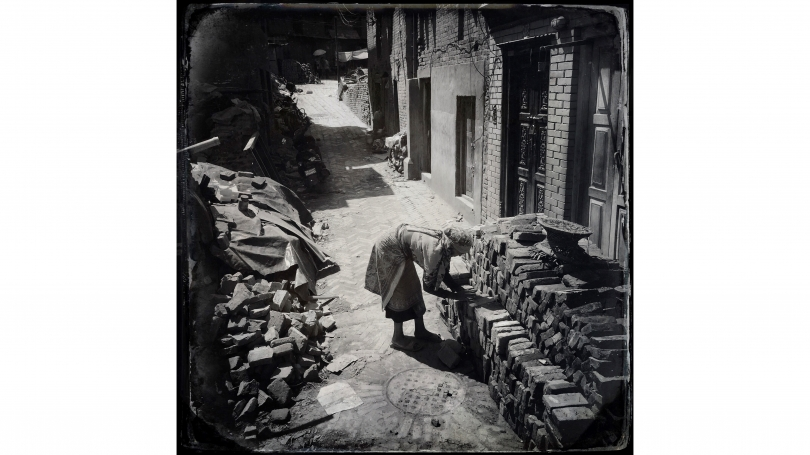 Kevin Bubriski, Latna Maya and her husband spent long days sorting bricks from their collapsed house. Broken pieces went to the left; usable bricks she lovingly stacked to the right, Bhaktapur, Nepal, 2015, archival pigment digital print.