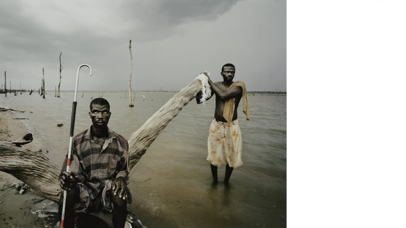 A photograph of two Black men on a beach. One stands in the water and the other on a large piece of drift wood. The man sitting is carrying a red and white striped cane.