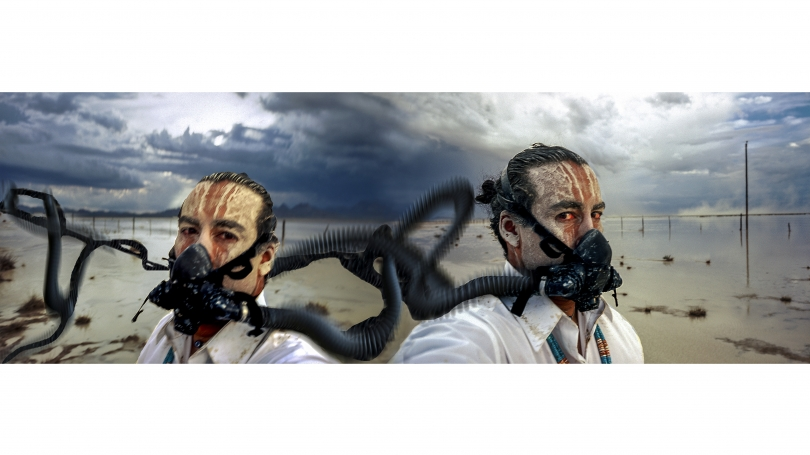 Two men, wearing hazmat suits, stand back to back on a deserted beach. It appears a storm is looming in the background as the sky and clouds are dark.