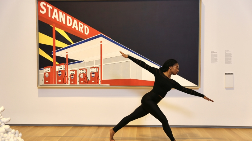 A dancer in all black clothing poses in front of a painting of a gas station.
