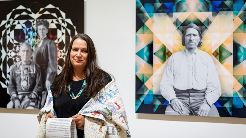"Gina Adams stands in front of her ""Ancestor Beadwork Prism"" series during a Broken Treaty Reading Performance"