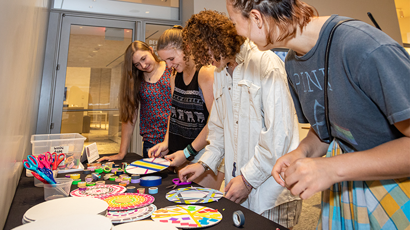 Four students gather around a table to do an artmaking project. On the table are cardboard circles, colorful washi tape, and scissors.